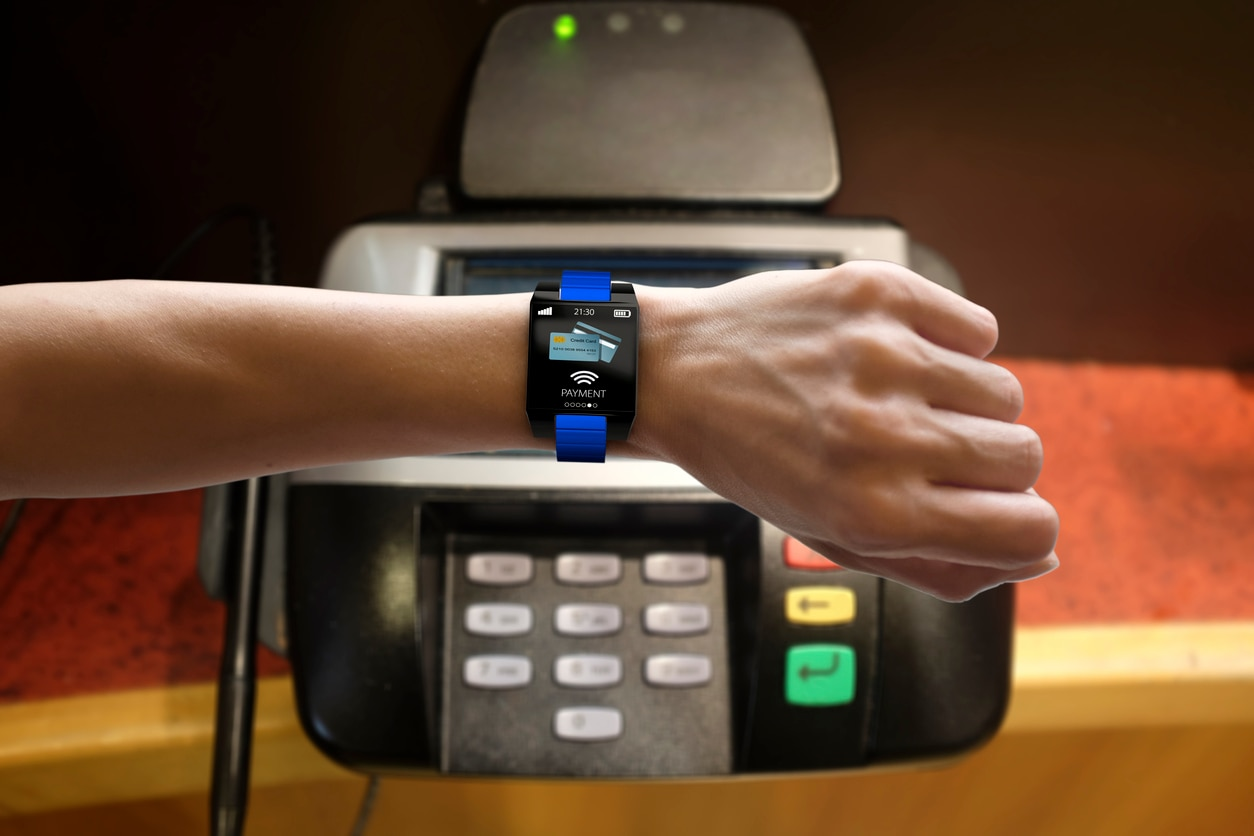 Smart Watch on woman's arm with Contactless payment and NFC technology application on screen with Electronic Reader.