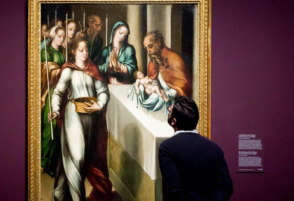 Fotografía de un visitante observando un cuadro del Divino Morales expuesto en El Prado con el patrocinio de la Fundación BBVA