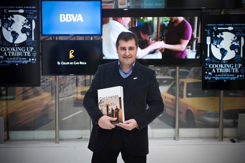 Fotografía de Josep Roca con el libro 'Cocinando un tributo', sobre la primera gira BBVA- El Celler de Can Roca
