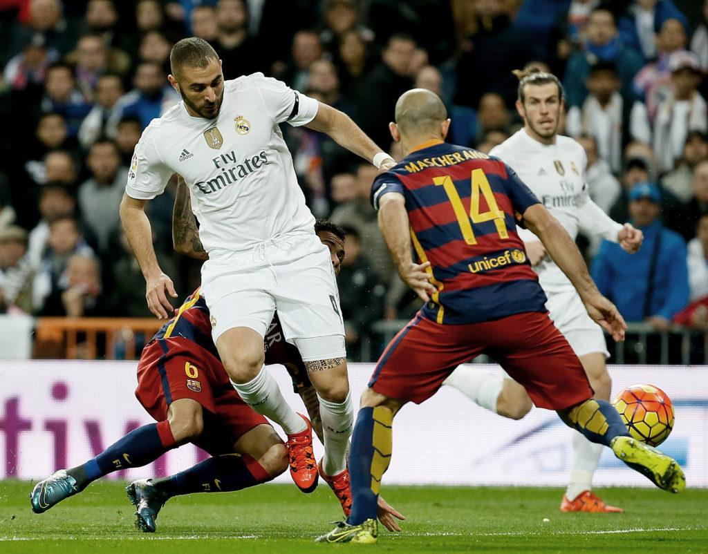 El delantero francés del Real Madrid Karim Benzema (i) pelea un balón con el defensa argentino del FC Barcelona Javier Mascherano en partido de Liga BBVA de la jornada 12º que les enfrenta en el Estadio Santiago Bernabéu. EFE