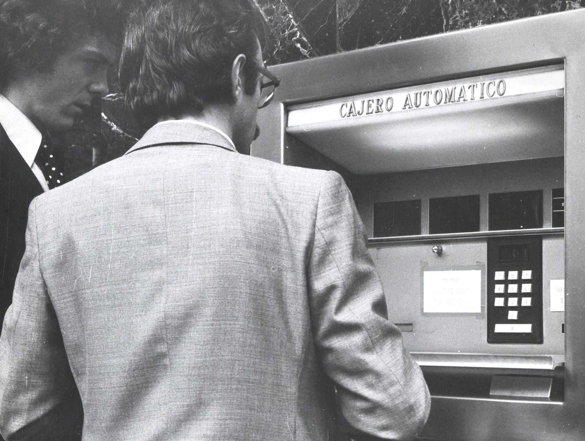 La fotografía data del 6 de junio de 1975 y fue realizada en Bilbao en la calle Gran Vía, 1. El impacto de los cajeros automáticos fue tal que sólo había que revisar los anuncios de prensa de la época. Puedes ver cómo se anunciaban en la siguiente fotografía...