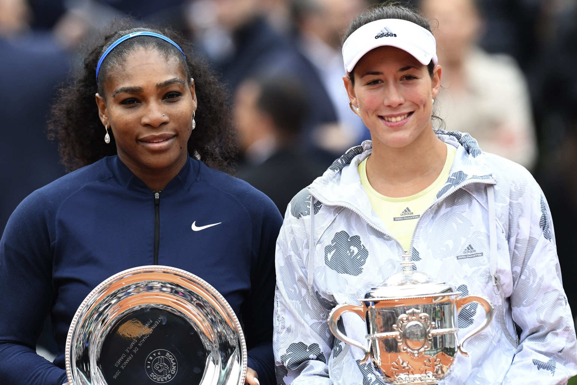 Fotografía de Garbiñe Muguruza y Serena Williams con copas de campeona y subcampeona de Roland Garros 2016