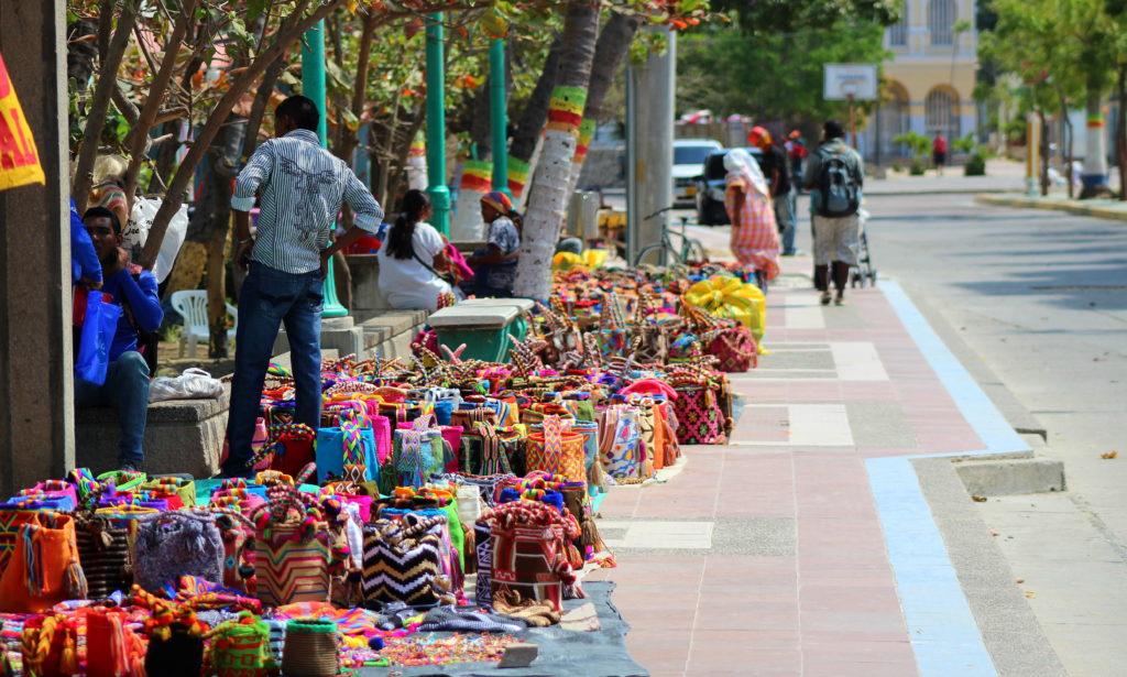 Foto de una calle de Colombia donde un grupo de personas venden mochilas, bolsos y hamacas tejidos a mano - Fundación Microfinanzas BBVA