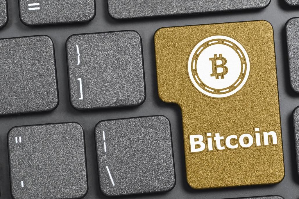 Fotografía de teclado con una Bitcoin, moneda virtual