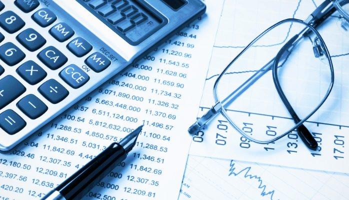 Fotografía de calculadora y gafas sobre hojas con números