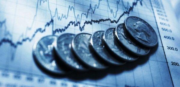 Fotografía de Monedas sobre hoja con gráfica del comportamiento de la economía