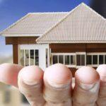 Fotografía de Edificio junto a casa sobre la mano de un hombre