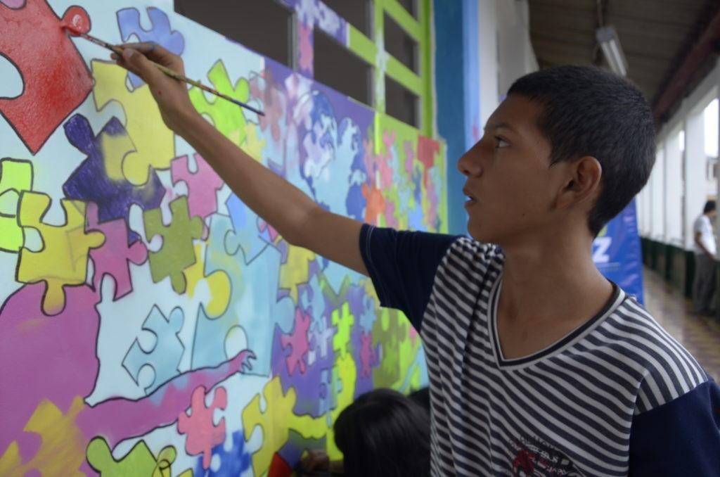 Fotografía de Estudiante de la Rafael Uribe Uribe pintando un mural de rompecabezas