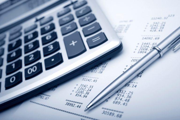 Fotografía de Impuestos en la reforma tributaria, calculadora sobre facturas y esféro