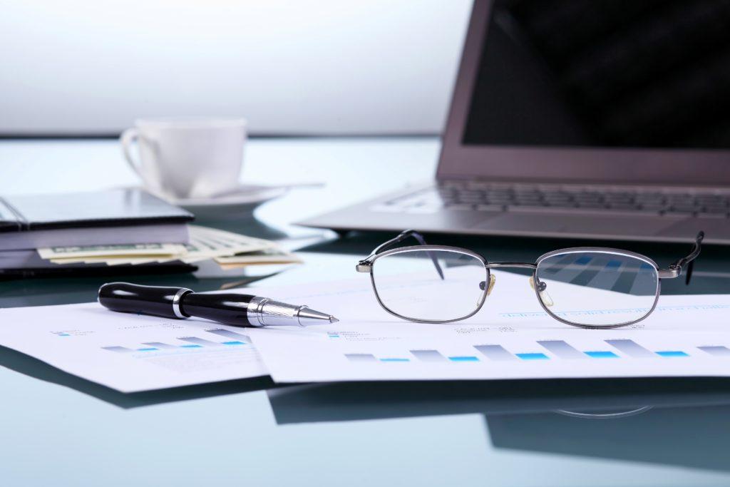Fotografía de Computador junto a gafas e informes financieros