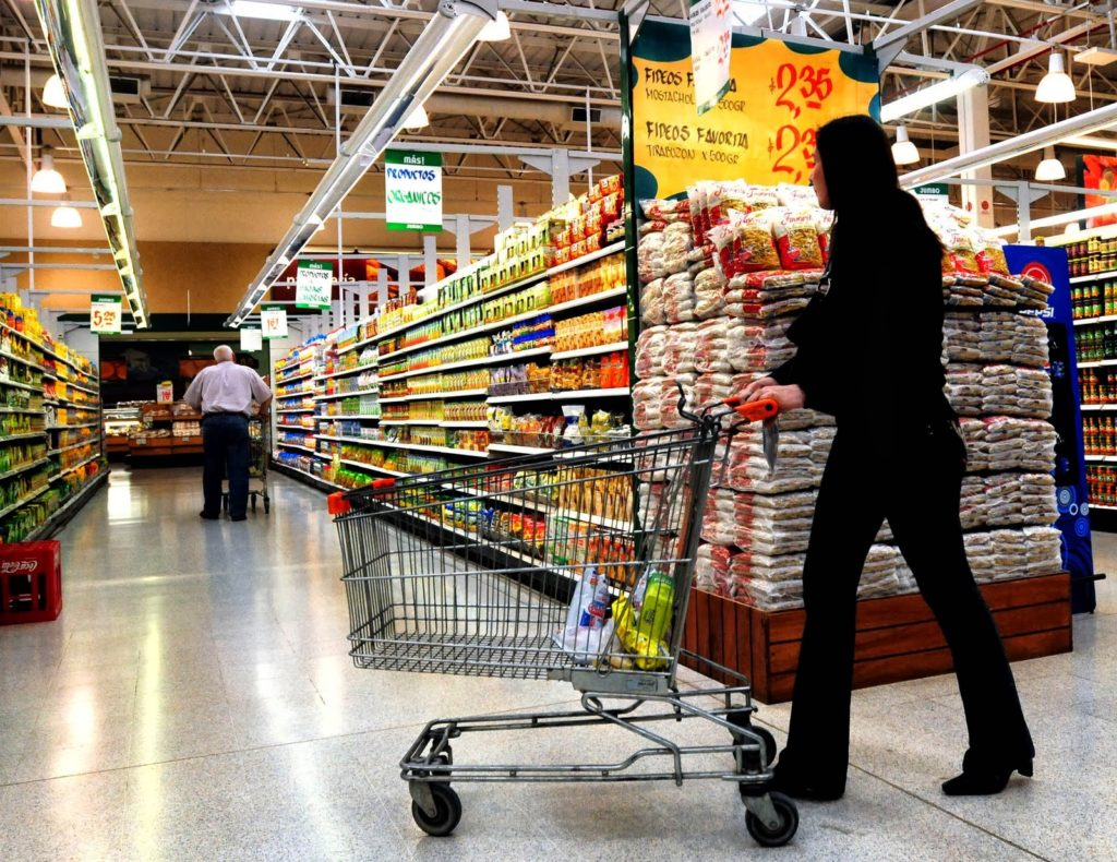 Fotografía de Mujer conduciendo un carrito de compras en un supermercado