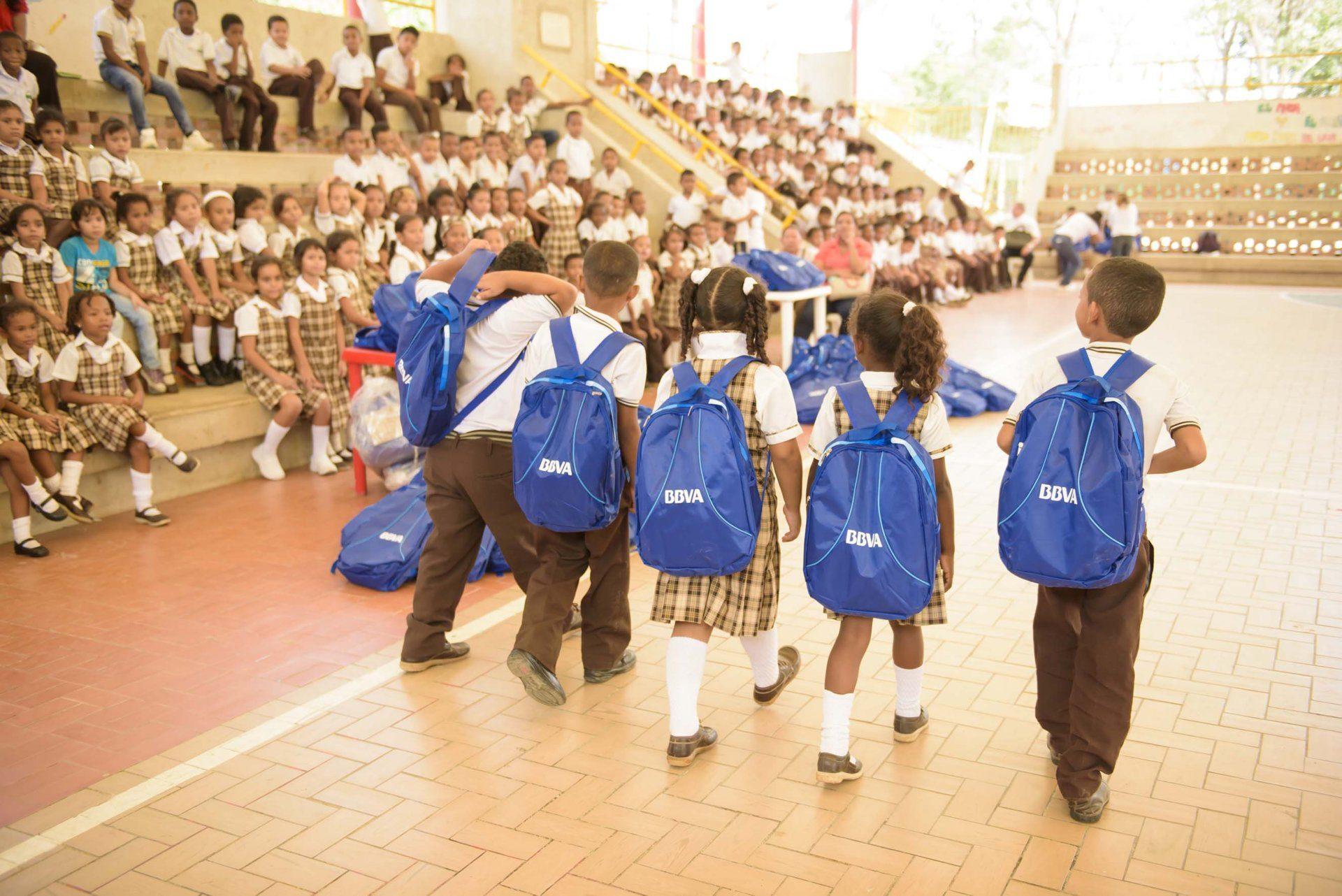 ninos-caminan-con-morrales-que-tienen-elementos-escolares-donados-por-bbva