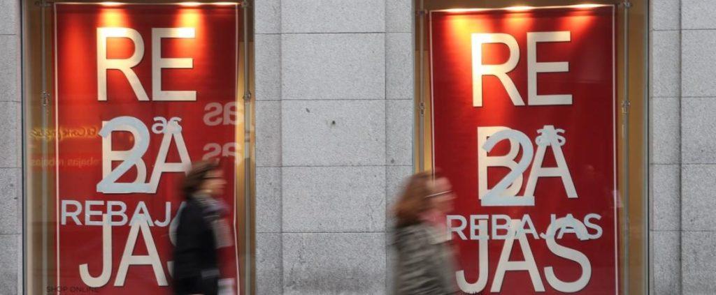 Fotografía de dos mujeres pasan ante los escaparates de un conocido centro comercial que anuncia el segundo periodo de rebajas