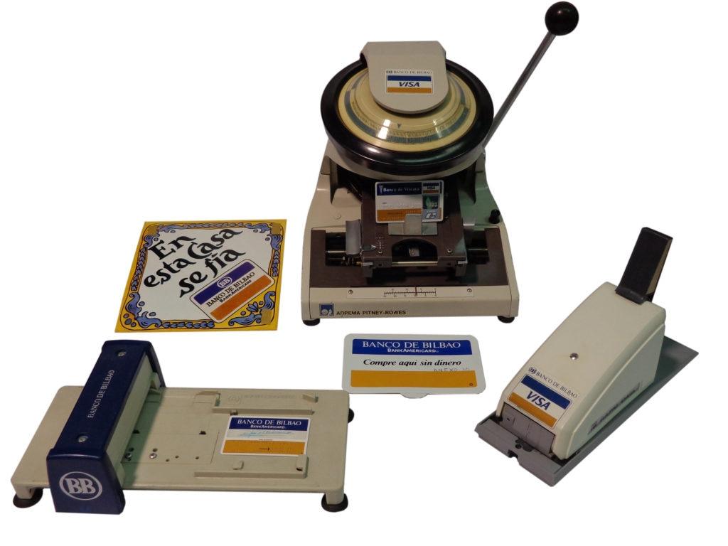 La primera máquina estampadora de tarjetas bancarias que hubo en España (año 1971). El Banco de Bilbao fue el pionero en esta materia. Vemos aquí el primer y segundo modelo de bacaladera