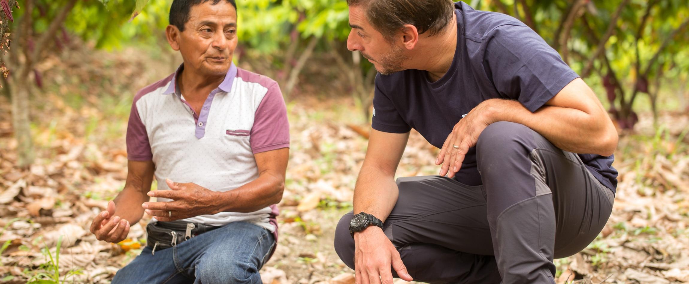Jordi Roca escucha al experto de cacao Oscar Velásquez hablando sobre la sustitución que se hace a través de injertos