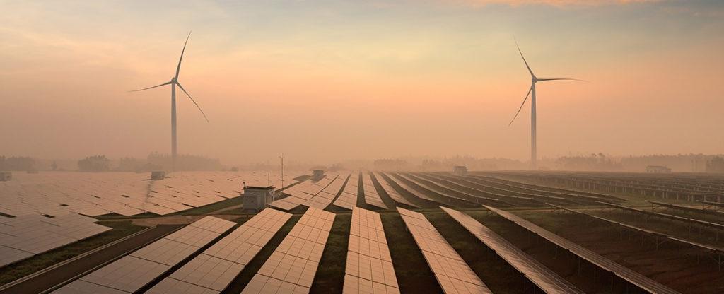 Fotografía de paneles solares y molinos de viento para ilustrar un artículo sobre financiación verde en BBVA
