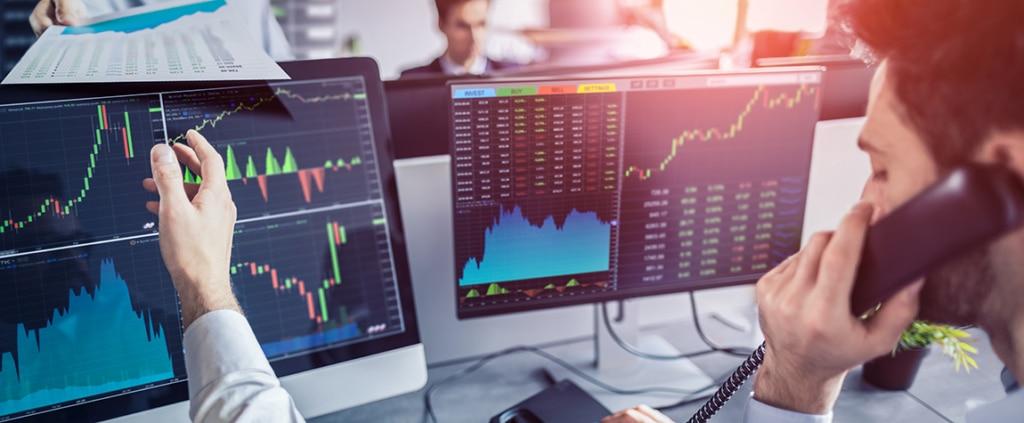 Fotografía de trader trabajando, ordenador, gráficos, teléfono