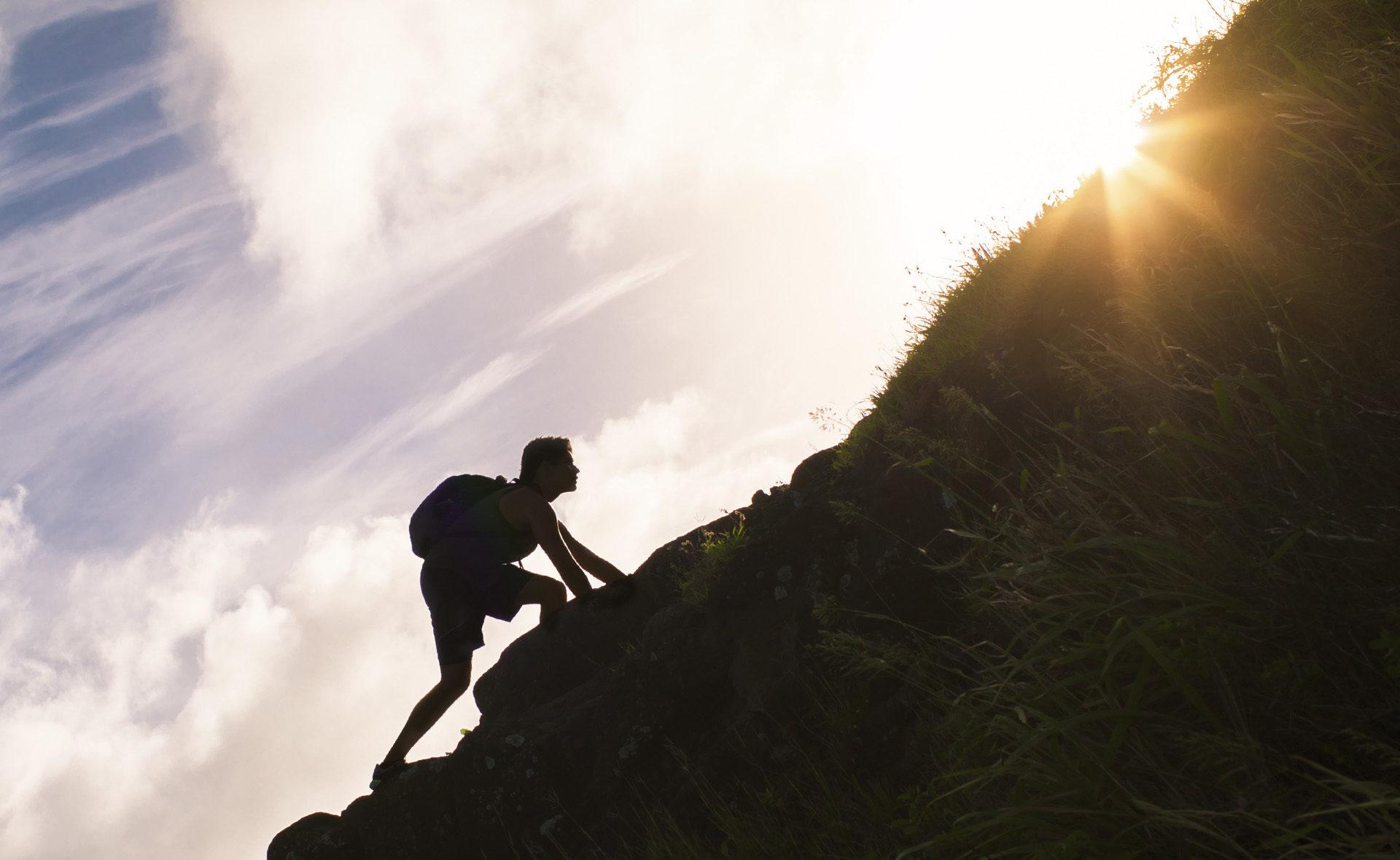 fotografía de hombre escalando montaña verde BBVA