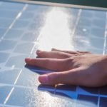 Human hand touching a solar panel