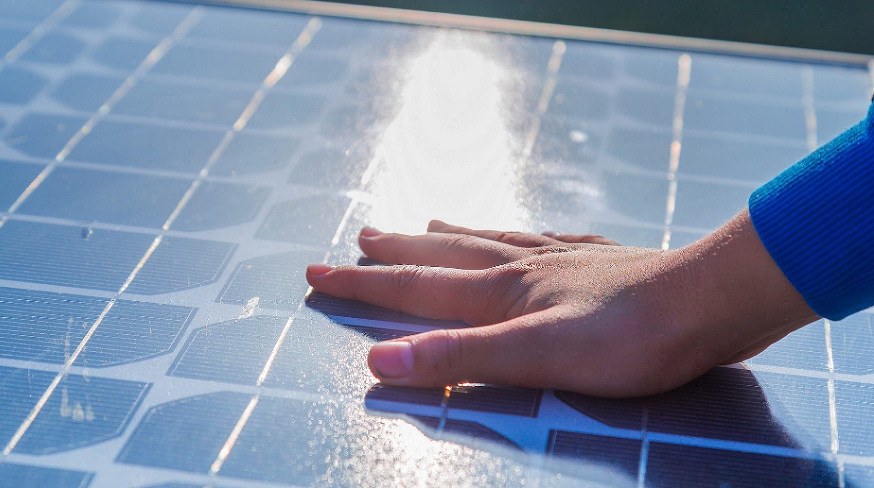 Human hand touching a solar panel