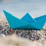 Fotografía de Barco, papel, playa, piedras, BBVA, sostenible, orilla, azul