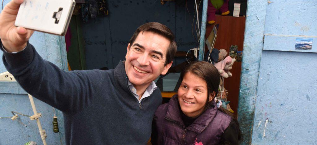 Fotografía del presidente de BBVA, Carlos Torres Vila, con Jéssica Hernández y su hija en su taller de costura