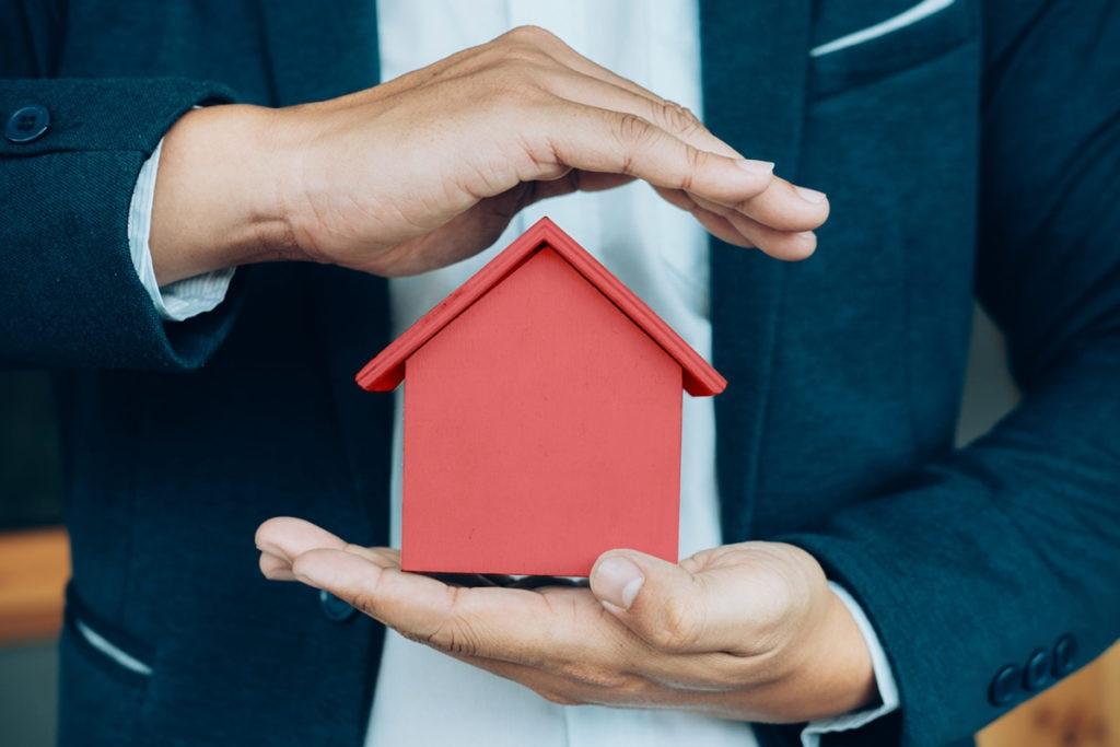 Business man hand hold the house model saving small house. seguro multiriesgo