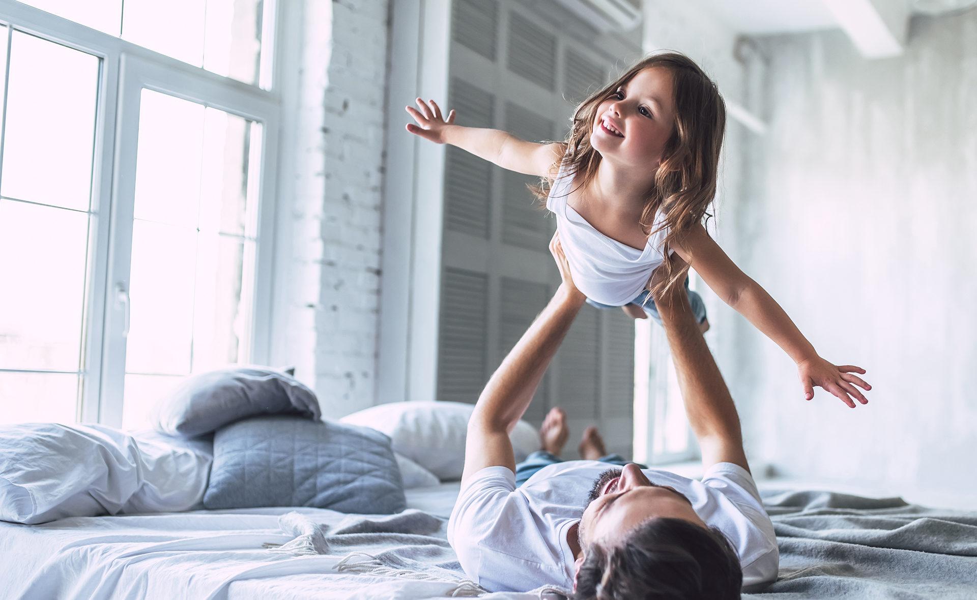 Apertura-dia-niña-educación-financiera-familia-hija-volar-cama-padres
