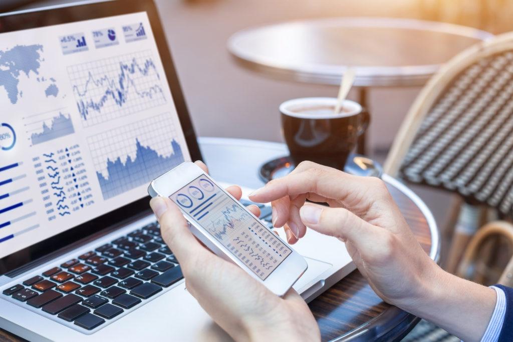 Businesswoman analyzing stock market KPI with BI, computer, smartphone screen