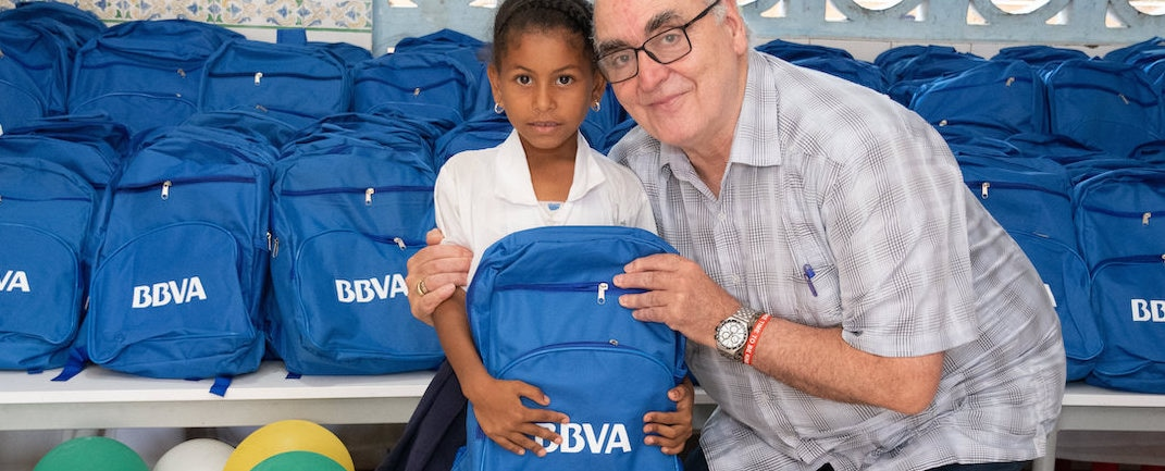 el gerente general de la fundación Fe y Alegría, Víctor Murillo Urraca entrega un morral a una de las niñas del colegio Luis Felipe Cabrera, que atiende esta fundación en la zona insular de Cartagena.
