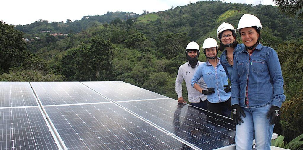 La ingeniera Yuliany García, acompañada de sus socias en la instalación de un panel en zona rural de Santander.