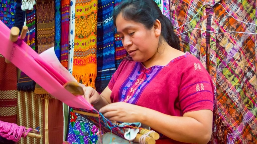 Mayan woman weaving textiles for sale in a market