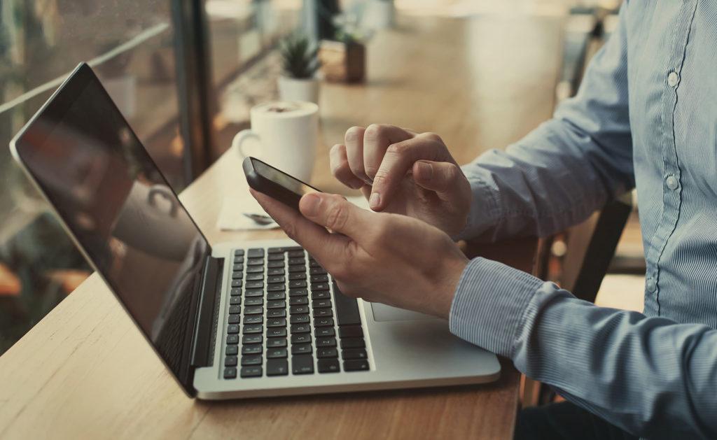 Fotografía de persona con móvil en la mano y ordenador delante BBVA