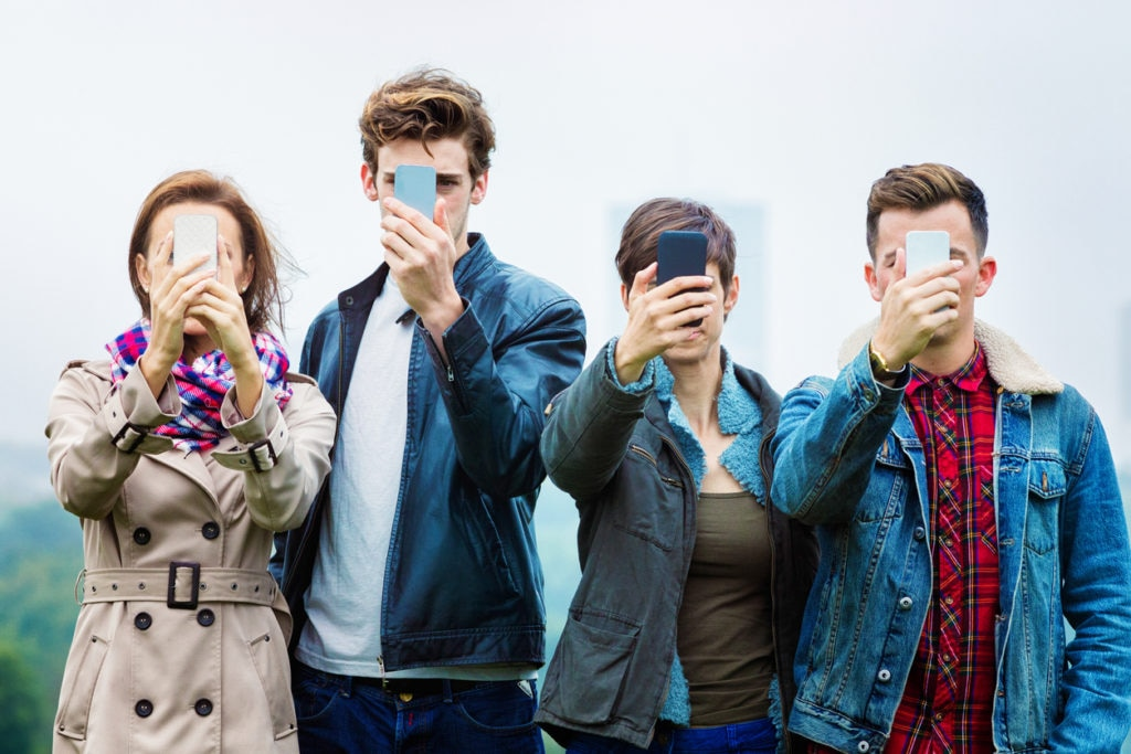 bbva Four friends shooting selfies on their mobile phones