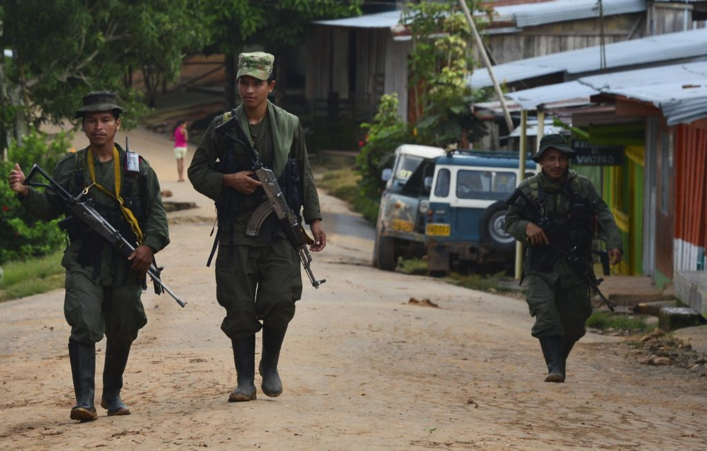 Image of Armed FARC fighters on a trek across one of the Colombian municipalities without State presence.
