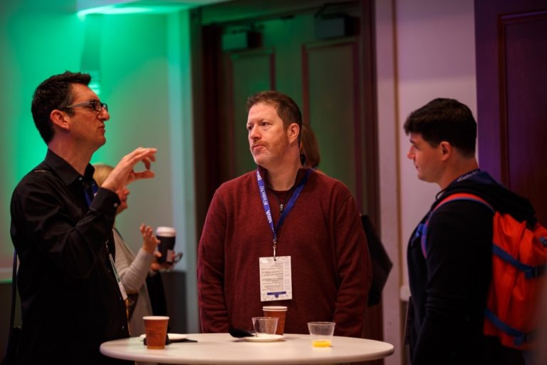 A photo of Fintech University attendees interacting during a coffee and networking session.