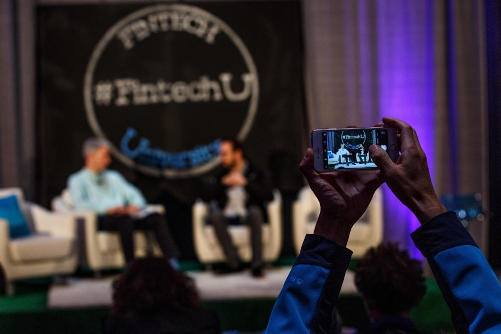 A photo of an attendee taking a picture of panelists at Fintech University.