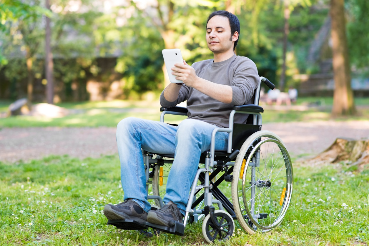 Disabled man using a tablet in a park